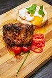 A junção da carne de porco serviu com tomators e ovo do bebê na placa de madeira Imagem de Stock Royalty Free