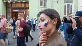 Girls draw flags on soccer fans` faces. JUN 16, 2018, MOSCOW, RUSSIA: Girls draw flags on soccer fans` faces. FIFA World Cup 2018 stock footage