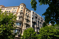 The junction of modern and old. Beautiful building peeps through the trees, Barcelona, Spain Royalty Free Stock Photography