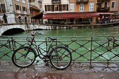 June 2, 2016 - Annecy, France : A bicycle leaning a rail by the river in the city. Background royalty free stock photography