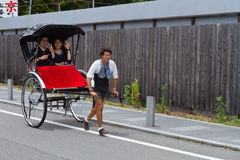 June 2012 - Arashiyama, Japan: An asian man pulling a Pulled rickshaw with two people sitting waving at the camera Royalty Free Stock Photo