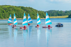 Children in sailing boats on reservoir lake. Royalty Free Stock Photos