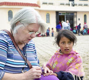 June 2016, cultural diversity in Riobamba, Ecuador. Senior Caucasian woman paints a young girl's fingernails in a church courtyard in a project near Riobamba Stock Image