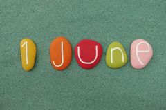 1 June, calendar date composed with multi colored stones over green sand. 1 June, a date to remember with a composition of multi colored stones over green sand royalty free stock photos