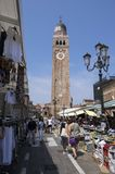 June 15, 2017 market in street in fCathedrale di Santa Maria Assunta, church clock tower in Chioggia, Italy, sunny day, blue sky Royalty Free Stock Photography