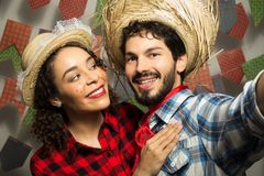 June Party is Festa Junina in Brazil. Passionate couple is photographing with cellphone or camera. Man does selfie with girlfriend. June Party or Festa Junina in royalty free stock image