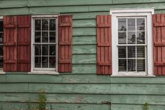 JUNE 26, 2017 - SAVANNAH GEORGIA - Historic siding of home features red shudders and green siding. Detail, shutters stock photography