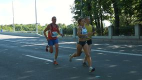 30 June 2019 St. Petersburg, Strong hardy girl running a marathon in slow motion. Strong hardy girl in short shorts running a marathon in slow motion with two stock footage