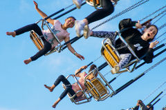 Teenagers ride swing chairs at Hastings fun fair Stock Photos