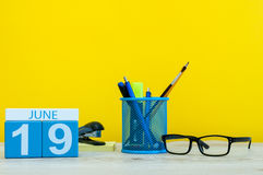 June 19th. Day 19 of month, calendar on yellow background with office suplies. Summer time at work Royalty Free Stock Photos