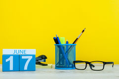 June 17th. Day 17 of month, calendar on yellow background with office suplies. Summer time at work Stock Photo