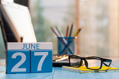 June 27th. Day 27 of month, wooden color calendar on workaholic workplace background. Summer time. Empty space for text Stock Images
