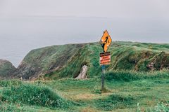 Warning signs of slippery surface and unprotected edges at the iconic Dunquin harbour pier surroundings in county Kerry
