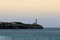 June 16th, 2017, Porto Colom, Mallorca, Spain - coastline view with a lighthouse on top of the hill at sunset. June 16th, 2017, Porto Colom, Mallorca, Spain Royalty Free Stock Images