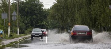June 21, Vyshenky Ukraine. Consequences of the shower. Car splashes through a large puddle on a flooded street. stock photo