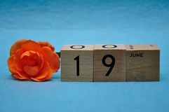 19 June on wooden blocks with an orange rose. On a blue background royalty free stock image