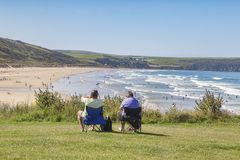 Summer Day Woolacombe. 17 June 2017: Woolacombe, North Devon, England, UK - Couple sit overlooking the beach as people enjoy the sunshine on one of the hottest Stock Photos