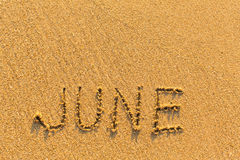 June - word inscription on the gold sand beach. Stock Images
