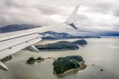 Plane wing over an ocean in Alaska Stock Photography