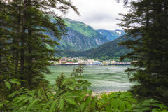 Juneau Alaska seen from Douglas Island. On the other side of Gastineau Channel .  Majestic mountain range with lush rainforest greens of the plants and trees Royalty Free Stock Photography