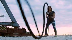 Jung, athletisch, Frau, führt Stärkeübungen mithilfe eines starken, sportlichen Seils durch An der Dämmerung entlang dem Sandpier stock footage