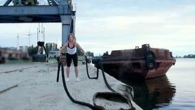 Jung, athletisch, Frau, führt Stärkeübungen mithilfe eines starken, sportlichen Seils durch An der Dämmerung entlang dem Sandpier stock video