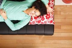Jung brasilianische Frau, die auf dem Sofa schläft Lizenzfreies Stockfoto