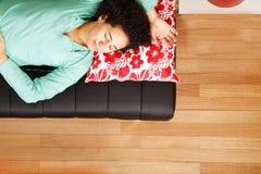 Jung brasilianische Frau, die auf dem Sofa schläft Lizenzfreie Stockfotografie