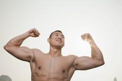 Jung, lächelnd, hemdloser junger Mann, der seine Muskeln mit den Armen angehoben biegt   draußen in Peking, China Stockfoto