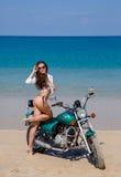 Jung, sexuell, das Mädchen auf dem Motorrad, auf einem Strand Stockfotografie
