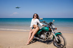 Jung, sexuell, das Mädchen auf dem Motorrad, das Fliegenflugzeug, an Lizenzfreies Stockfoto