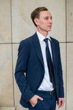 Jung und erfolgreich Hübscher junger Geschäftsmann, der beim mit Bürogebäude im Hintergrund draußen gehen weg schaut Lizenzfreie Stockfotos