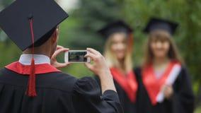 Jungakademiker im Umhang und Kappe, die Fotos von Mädchen auf Mobiltelefon, Freundschaft macht stock video