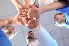Junge Ärzte, die Hände, Ansicht von unten zusammenfügen Schattenbilder der Leute auf Hintergrund des blauen Himmels stockbilder