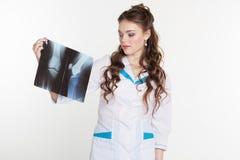 Junge Ärztin, die das Röntgenstrahlbild betrachtet Stockfotos