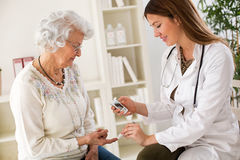 Junge Ärztin, die DiabetesBlutprobe auf älterer Frau macht Stockbilder