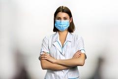 Junge Ärztin mit den Armen kreuzte stockfotos