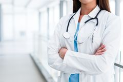 Junge Ärztin-Posing With Crossed-Hände am Krankenhaus Innen Stockbilder