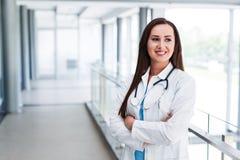 Junge Ärztin-Posing With Crossed-Hände am Krankenhaus Innen Lizenzfreie Stockbilder