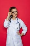 Junge Ärztin On Red Background Lizenzfreies Stockbild