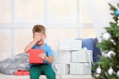 Junge öffnet einen Kasten mit einem Weihnachtsgeschenk stockbild