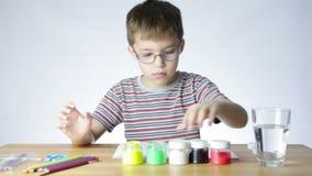 Junge öffnet Gläser mit Farbe stock footage