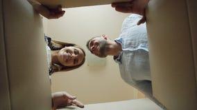 Junge Öffnungspappschachtel des glücklichen Paars nach Verlegung und Schauen inner und Nehmen der Schale im neuen Haus stock video footage