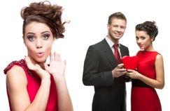 Junge überraschten die Frau und Paare, die rotes Herz auf Weißrückseite halten Lizenzfreie Stockfotografie