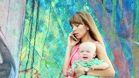 Junge überzeugte Mutter spricht am Telefon, das Sohn hält stock video footage