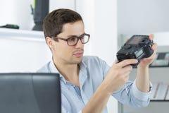 Junge überzeugte Technikerfestlegung und Reinigung digitales cameralense Stockfotografie