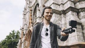 Junge aber erfahrener Reisender macht selfie nahe der Kirche in der Stadt Das Kerllächeln und -blicke glücklich Lizenzfreie Stockbilder