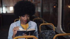 Junge afrikanische Amerikanerin oder Fluggast-Lesebuch im öffentlichen Nahverkehr, Steadicam-Schuss Schwungbewegung Stadt stock video footage