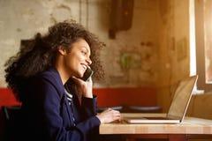 Junge afrikanische Frau, die im Café sich entspannt und Telefonanruf macht stockbild