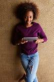 Junge afrikanische Frau, die sich mit digitaler Tablette hinlegt Stockbilder